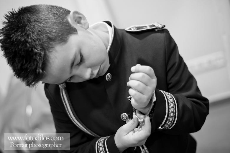 Abrochando los botones del traje de comunión